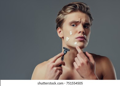 Handsome young man isolated. Portrait of shirtless muscular man is standing on grey background with razor in hand while shaving. Men care concept. Get hurt while shaving.