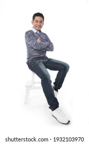 Handsome young man in jeans with arms crossed sitting wooden chair on white background
