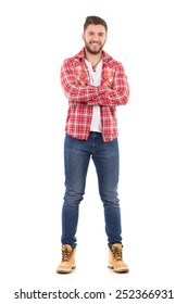Handsome young man in jeans and lumberjack shirt standing with arms crossed. Full length studio shot isolated on white.