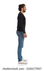 Handsome young man in jeans, sneakers and black jersey is standing relaxed, looking away and smiling. Full length studio shot isolated on white.