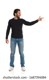 Handsome young man in jeans, sneakers and black blouse is standing, looking away and pointing at the side. Full length studio shot isolated on white.