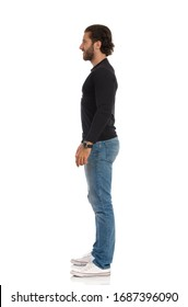 Handsome young man in jeans, sneakers and black jersey is standing with relaxed. Side view. Full length studio shot isolated on white.