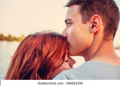 Handsome young man kissing his girlfriend near the river