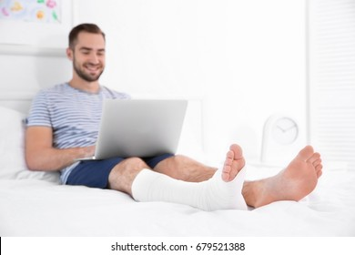 Handsome young man with laptop and bandaged leg sitting on bed at home