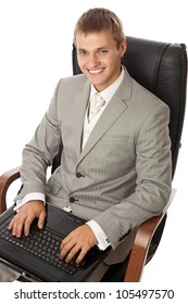Handsome young man with a laptop sitting in an armchair