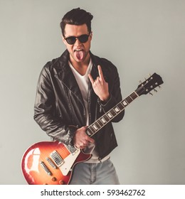 Handsome young man in leather jacket and sun glasses is holding a guitar and showing rock sign, on gray background