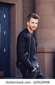 Handsome young man in leather jacket posing in city
