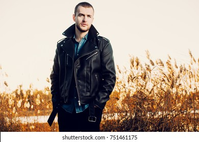 Handsome young man in leather jacket in the autumn park on a sunset. Seasonal fashion.