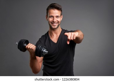 A handsome young man lifting weight smiling and pointing it to the camera