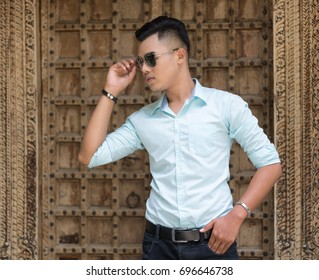 Handsome young man in light blue shirt with sun glasses.