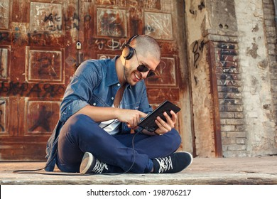 handsome young man listening to music with headphones via tablet PC