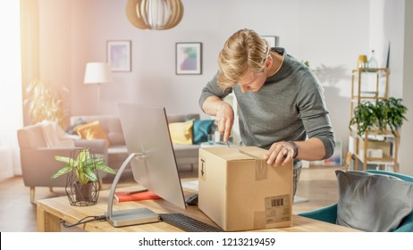 Handsome Young Man in Living Room with Cardboard Box Package, Opening it With Interest, Using Knife.