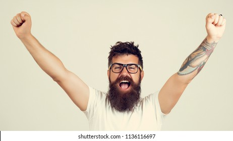 handsome young man with long beard and moustache with happy face in glasses and hands up, on grey background in studio, so shocked, extremely happy, wide open mouth in white T-shirt with raised hands