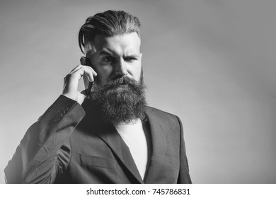 Handsome young man with long beard and moustache in black jacket speaking on mobile phone in studio on grey background