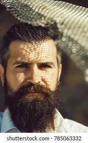 handsome young man with long beard and moustache on serious face with metallic net sunny day outdoor