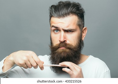 handsome young man with long dark haired beard and moustache on surprised scary face holding hair brush on grey background