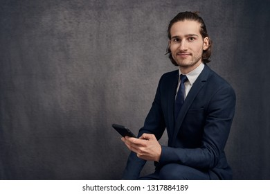 Handsome young man with long hair, wearing stylish suit and blue tie, holding smartphone in his hand, looking at camera with modest smile.