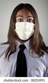 Handsome young man with long hair wearing a breathing mask for protection from germs and viruses