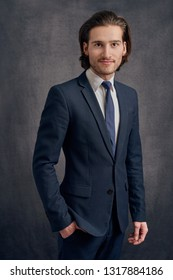 Handsome young man with long haircut in business suit with blue necktie, standing and looking at the camera