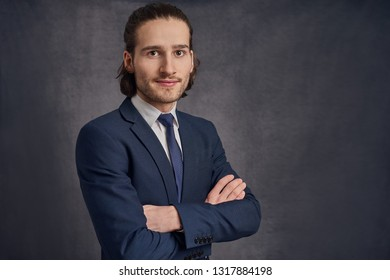 Handsome young man with long haircut in business suit with blue necktie, standing with his arms crossed against grey background with copy space and looking at camera.