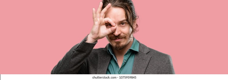 Handsome young man looking at camera through her fingers in ok gesture. Imitating binoculars, beautiful eyes and smile