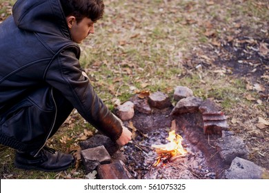 Handsome young man looking at the fire, smoldering fire, holding a book, paper, paper toss into the fire, a letter. Man dreams near the fire, the heat warms his hands. Horizontal shot.