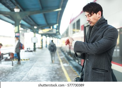 handsome young man looking at his watches standing on winter railway platform