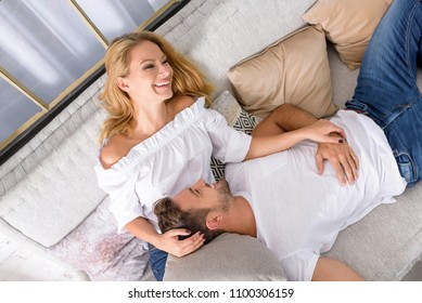 A handsome young man lying on the sofa with head on his girlfriends chest.