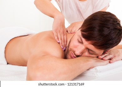 Handsome young man lying on his stomach in a spa having a shoulder massage