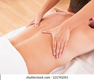 Handsome young man lying on his stomach in a spa having a back massage