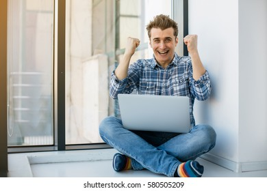 handsome young man lying on the floor with laptop in arms, enjoying a win or good news from the Internet