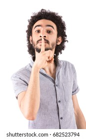 Handsome young man making silence sign, guy wearing gray t-shirt and jeans, isolated on white background
