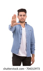 Handsome young man making stop sign and looking strait, guy wearing blue shirt and jeans, isolated on white background