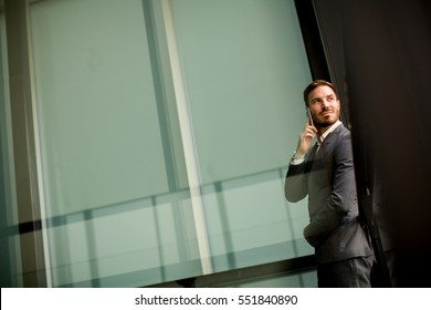 Handsome young man with mobile phone by office building