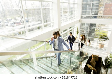 Handsome young man with mobile phone on stairs in modern office