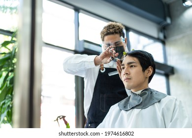 Handsome young man in modern salon getting haircut service from  stylist Asian male hairdresser wearing a face shield and mask for protection and practicing social distance during Covid 19 pandemic.