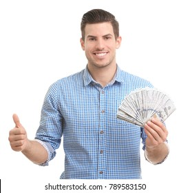 Handsome young man with money showing thumb up gesture on white background