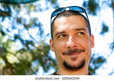 Handsome young man with moustache and beard and sunglasses enjoying in the park
