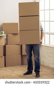 Handsome young man is moving, holding a cardboard boxes that covering him