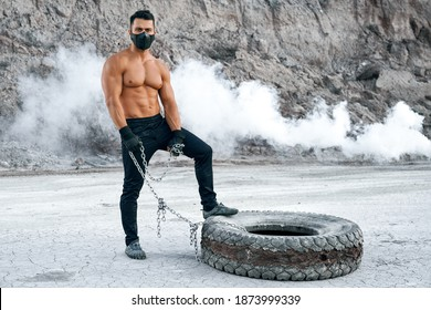 Handsome young man with muscular body posing outdoors while standing near big tyre. Strong guy wearing black face mask , sport pants and gloves.