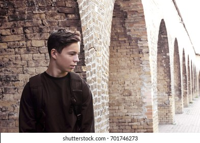 Handsome young man near a brick wall on a city street