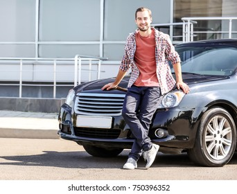 Handsome young man near car outdoors