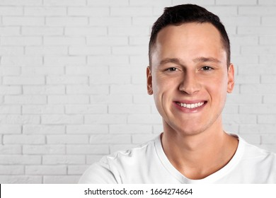 Handsome young man near white brick wall. Space for text