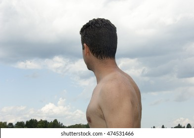 Handsome young man with no shirt, wet from swimming, looking away from the camera.