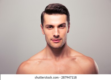 Handsome young man with nude torso looking at camera over gray background