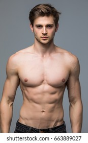 Handsome young man with nude torso looking at camera over gray