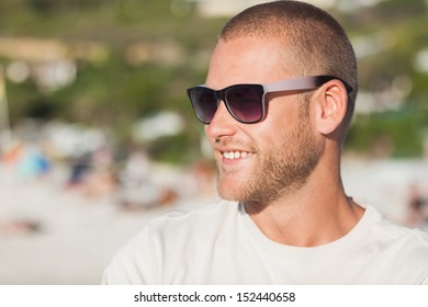 Handsome young man  on the beach wearing sunglasses looking away