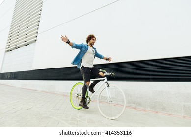 Handsome young man on bike without hands in the city. Bicycle concept