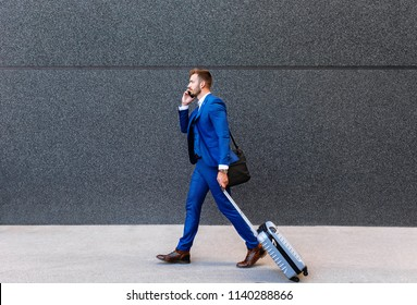 Handsome young man on business trip walking with his luggage and talking on phone at airport.