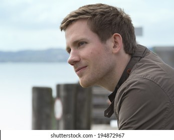 Handsome young man on a coastal pier Handsome young man on a coastal pier standing overlooking the water with a charismatic smile on his face and thoughtful expression, close up side view